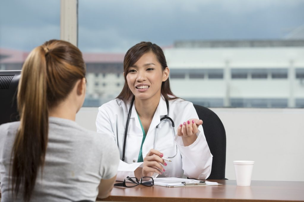 Female doctor sharing health screenings results with a patient in Singapore