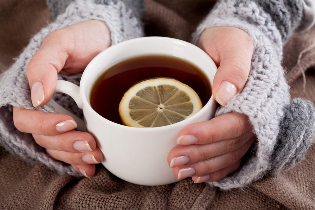 A woman holding a cup of warm lemon tea, which can soothe throat inflammation