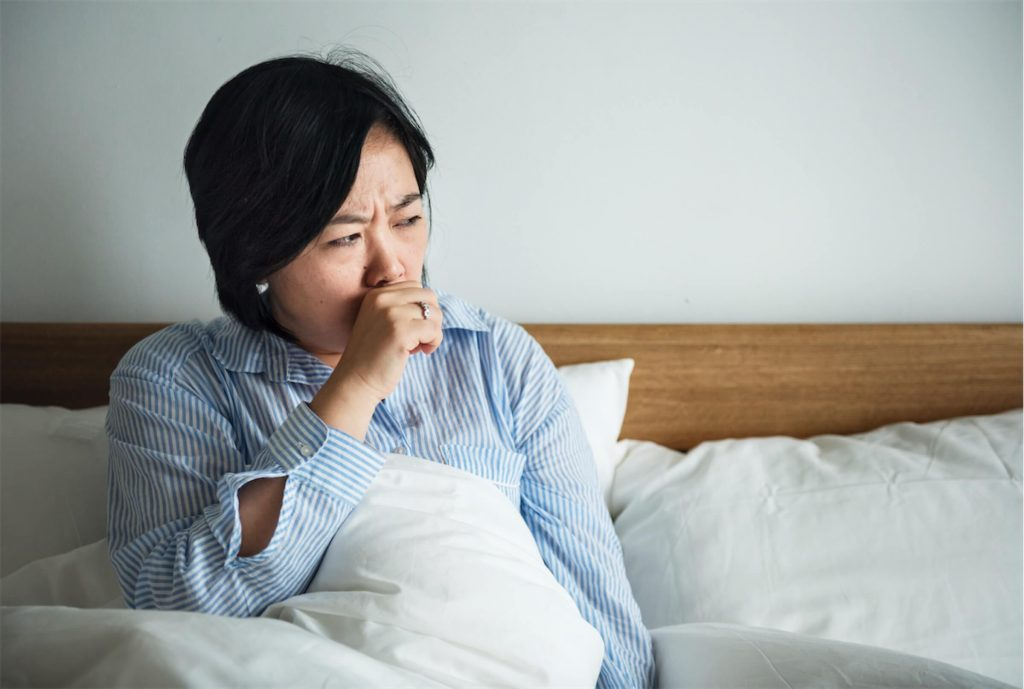 A woman coughing and suffering from throat inflammation