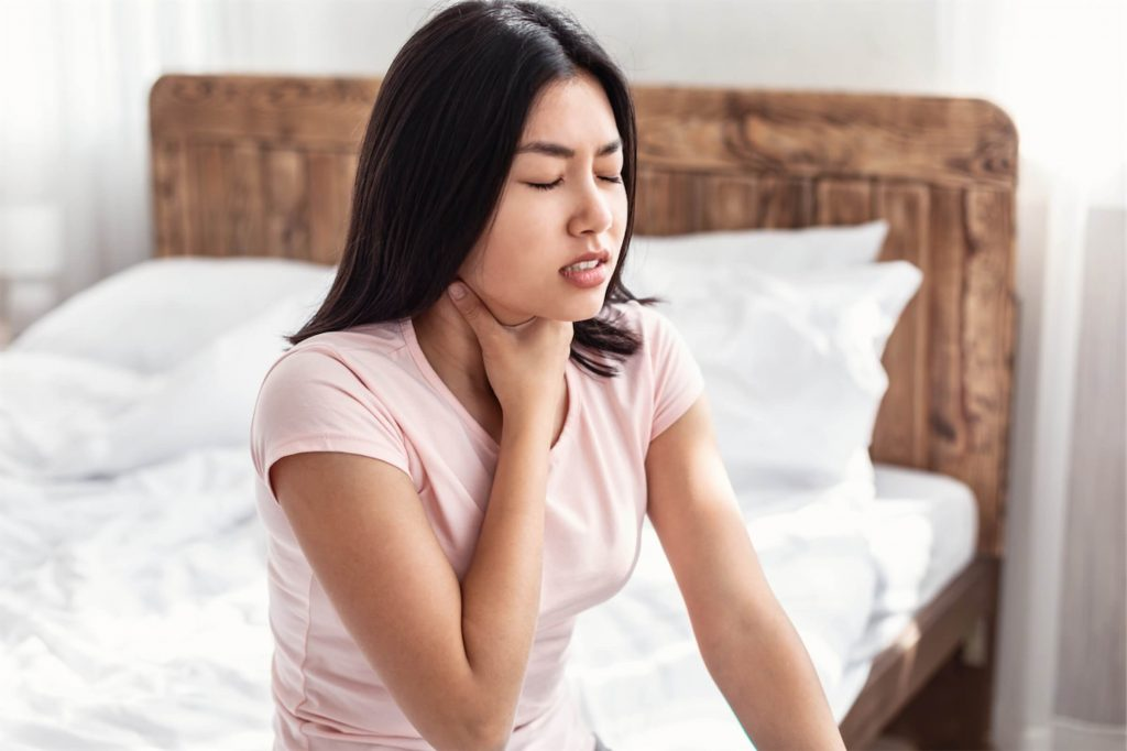Woman with throat inflammation holding her neck