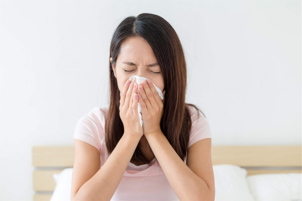 Woman suffering from whooping cough symptoms and sneezing into a tissue