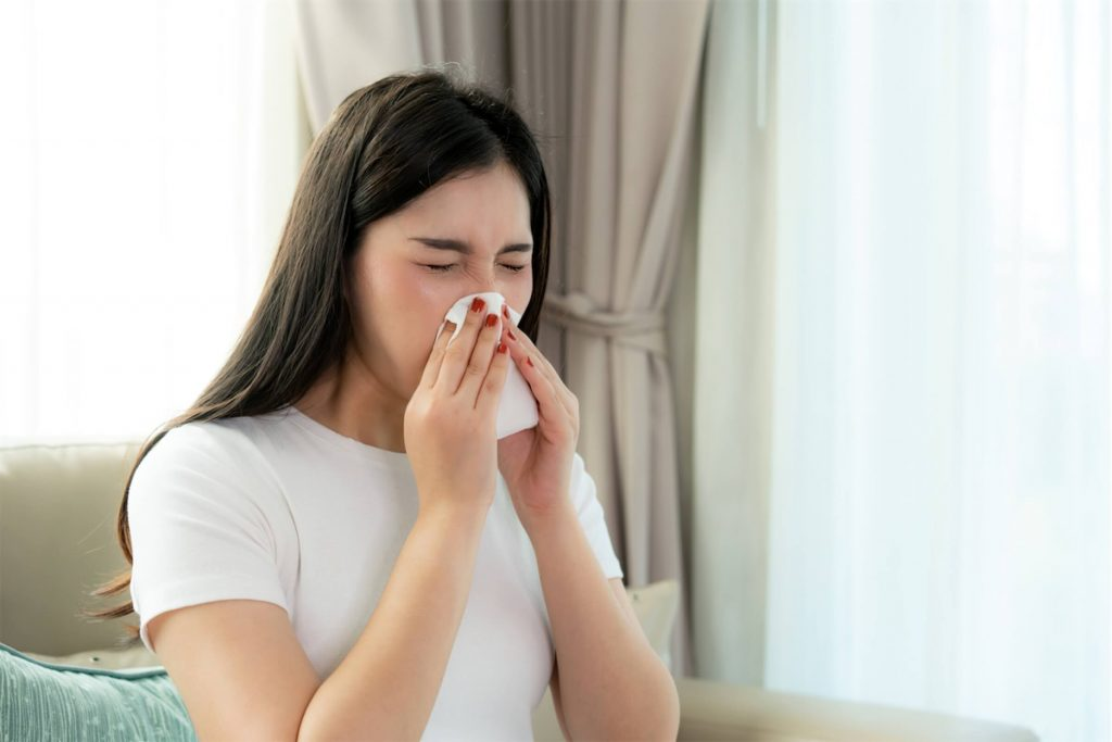 Woman blowing her nose into a tissue paper before using a nasal spray in Singapore.