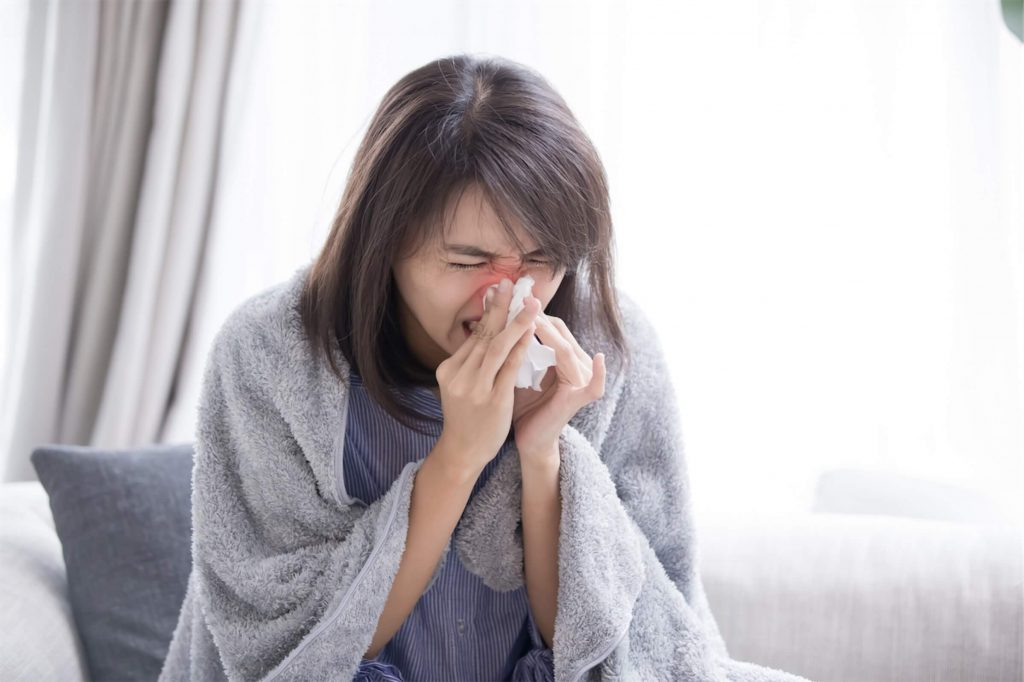 Woman sneezing and thinking of taking a decongestant to relieve her nasal congestion