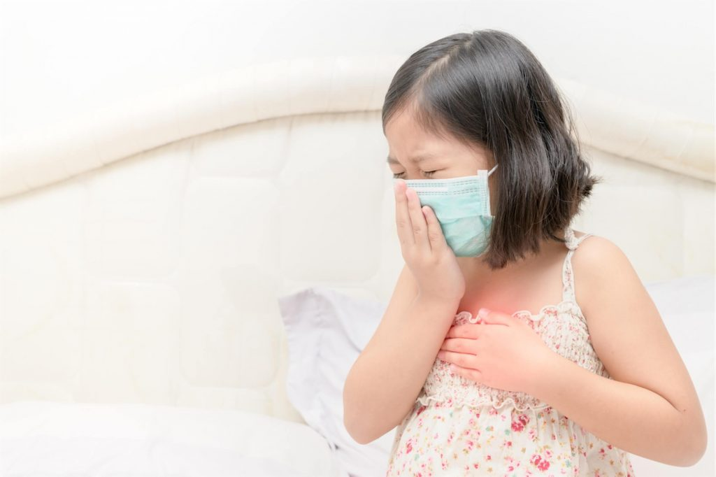 Young girl wearing a mask and coughing, likely suffering from the 100 days cough