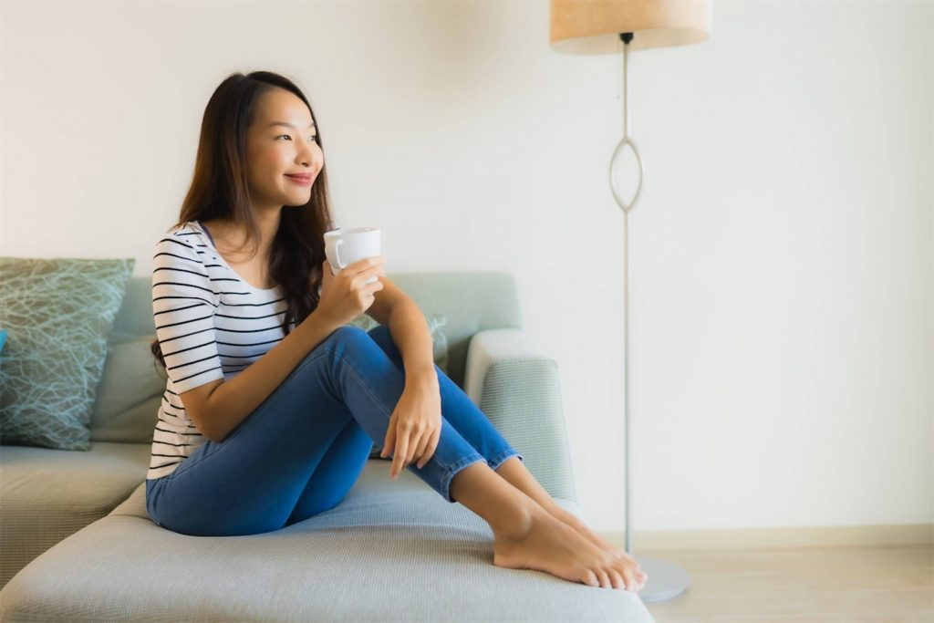 A woman sitting on a sofa while holding a cup of tea