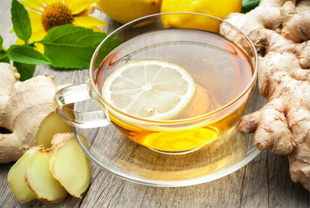 A cup of warm tea with ginger and lemon slices, which is good for soothing irritation caused by laryngitis