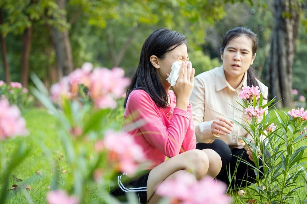 Woman sneezing and suffering from a runny nose due to pollen allergy