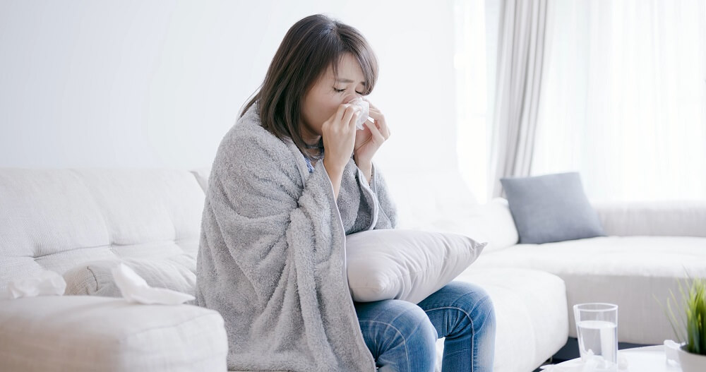 Woman cleaning her runny nose with a facial tissue
