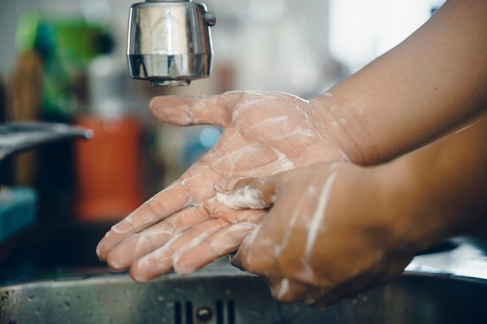 Person washing hands with soap at the basin