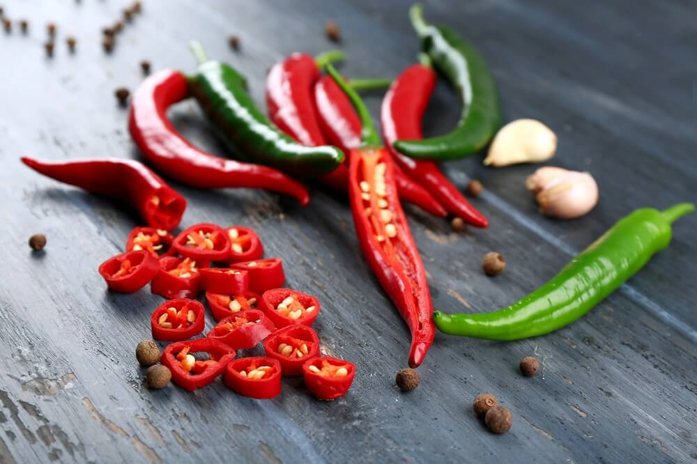 A few green and red chillis, which are a spicy ingredient that could provide sinus headache relief