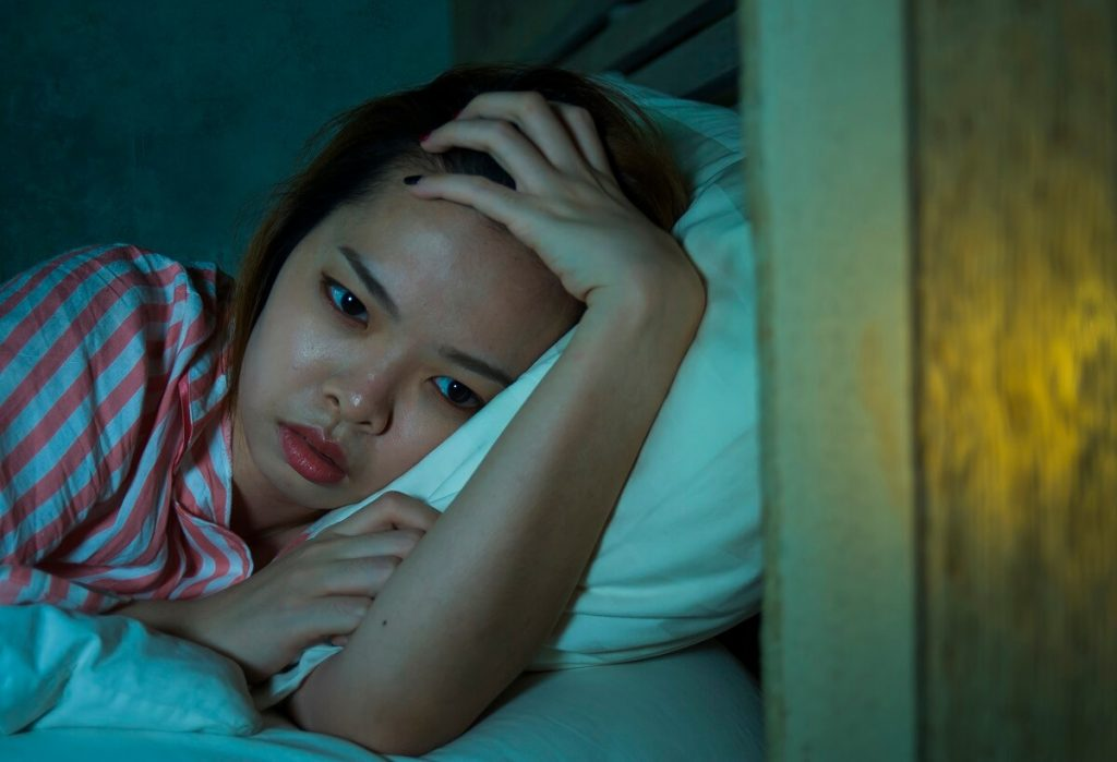 Woman looking moody in bed due to her depression
