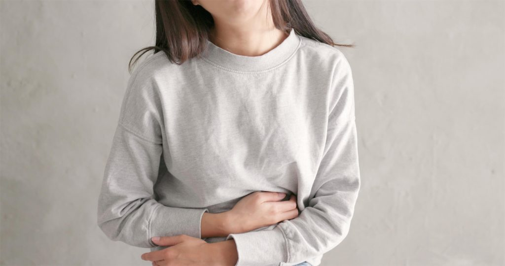 Woman having stomach problems, a physical symptom of generalised anxiety disorder