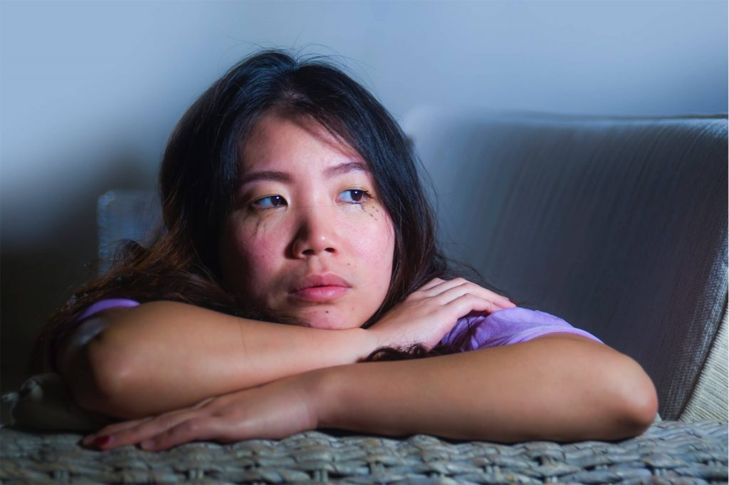 A young mother with postnatal depression looking tearful.