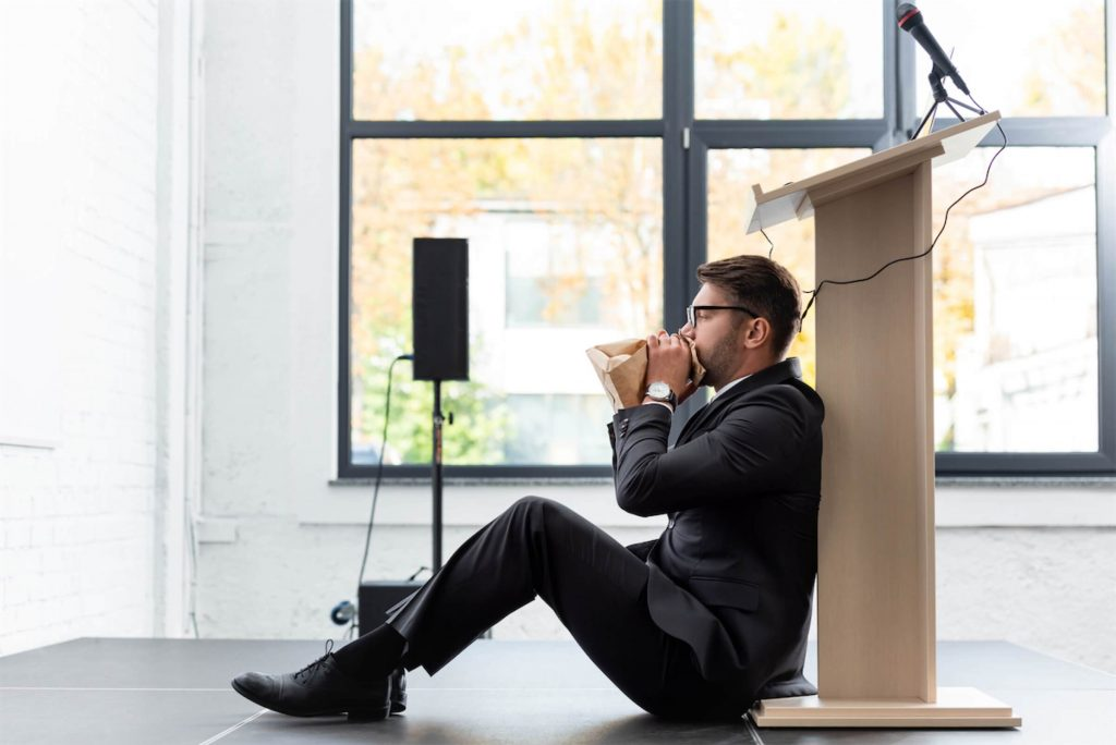 A man breathing into a paper bag as he deals with the social anxiety before making a speech