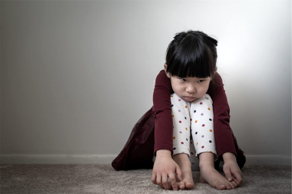 A girl sitting on the floor and feeling sad