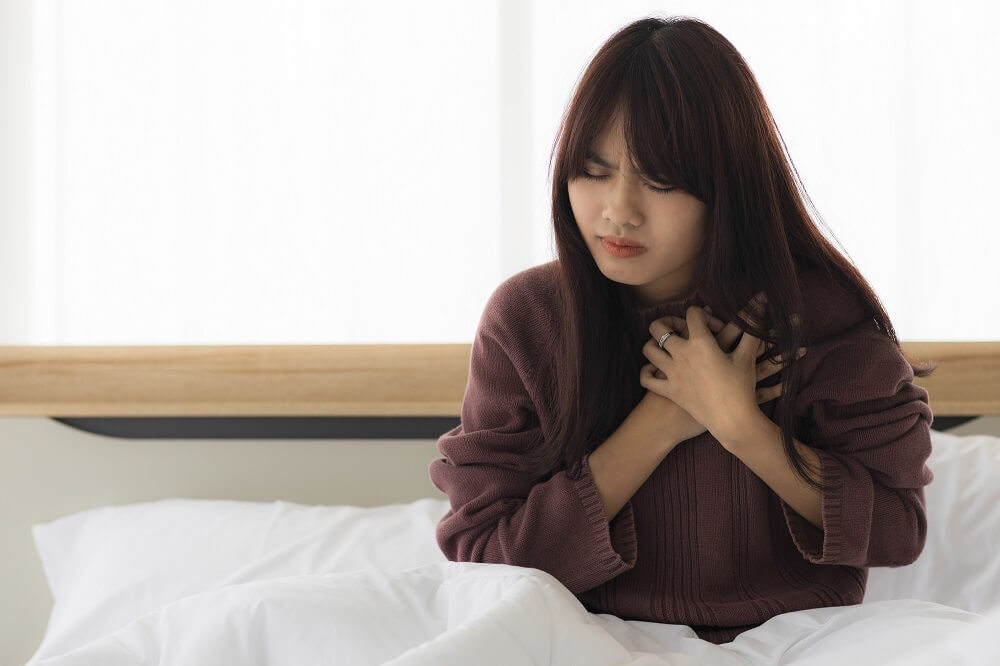 A woman clutching her chest and having chest pains, which is a sign of a panic attack