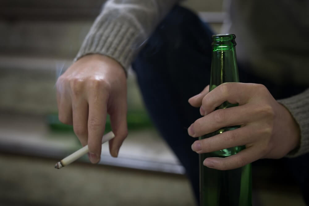 A man smoking and drinking alcohol, which are common causes of erectile dysfunction in Singapore