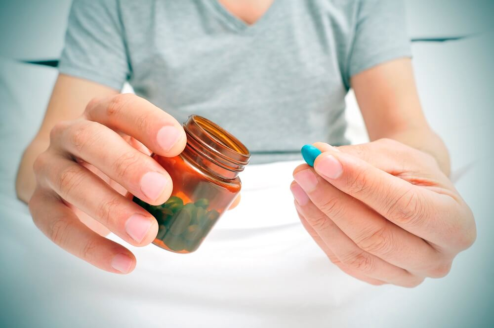 A man holding Viagra, the most common treatment for erectile dysfunction in Singapore