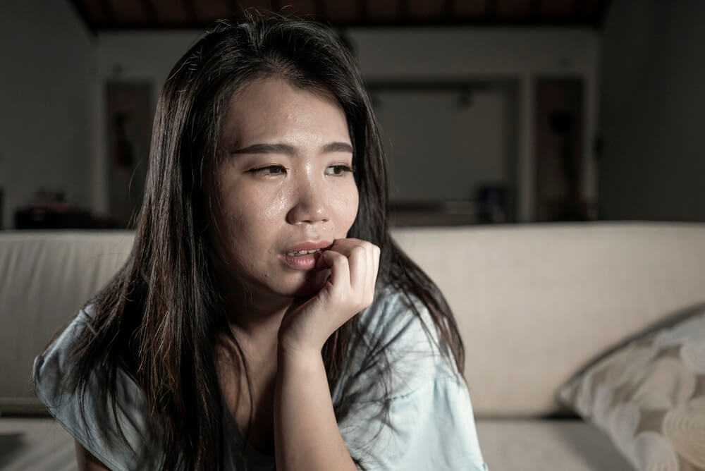 A mother with postnatal depression looking tearful and anxious