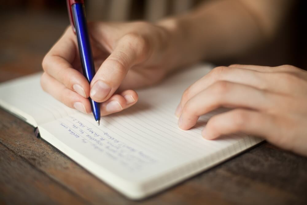 Person journaling her thoughts to help cope with her social anxiety