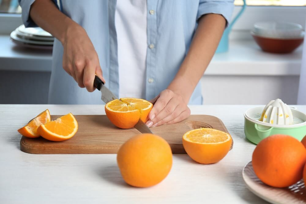 Person cutting oranges, a good source of fibre to help you maintain a healthy diet and cope with social anxiety