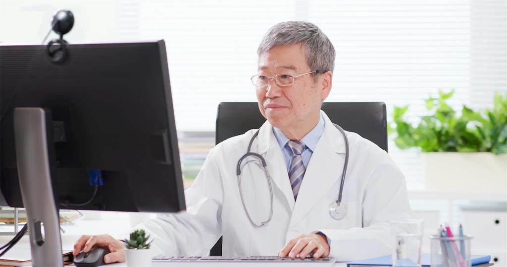 Asian doctor using a telehealth platform on his desktop computer